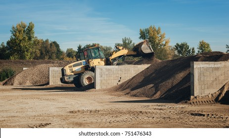 Bagger scooping gravel at construction aggregate dumps at concrete production plant