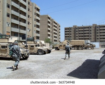 BAGHDAD, IRAQ - CIRCA AUGUST 2007: Unidentified soldiers walk through a parking area in a forward operating base near Sadr City during the height of the Iraq war