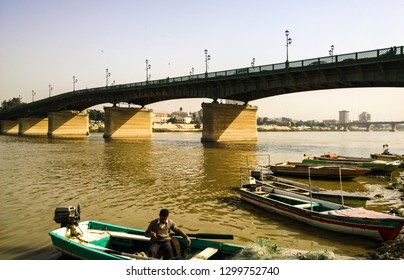 Baghdad, Iraq – January 1, 2019: picture for Tigris River in Baghdad city capital of Iraq country, and Alahrar Bridge and some boats on one of its side.and man on his boat