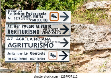 Bagno Vignoni, Italy - August 26, 2018: Medieval town by San Quirico d'Orcia in Val d'Orcia, Tuscany with closeup of direction signs for Agriturismo hotels
