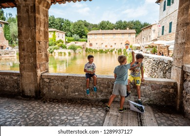 Bagno Vignoni, Italy - August 26, 2018: Medieval town by San Quirico d'Orcia in Val d'Orcia, Tuscany with people tourists young boys children by ruins and historical buildings