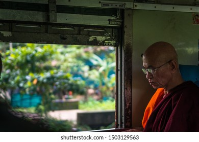 bago, myanmar. 15th august, 2019: portrait of pensive old monk while looking out window