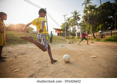 BAGO, MYANMAR - JAN 19, 2014: Unidentified Burmese children play soccer on dirt field.