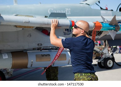 BAGOTVILLE, QUEBEC/CANADA  - JUNE 22: Bagotville Airshow. A technician check a missil on Royal Canadian Air Force (RCAF) CF-18 in Bagotville, Quebec, Canada on June 22, 2013.