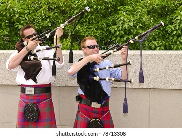 Bagpipe duo wearing kilts and having fun  between songs as they entertain tourists in Ottawa, Canada.