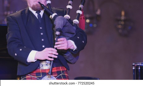 Bagpipe player plays musical instrument at the stage