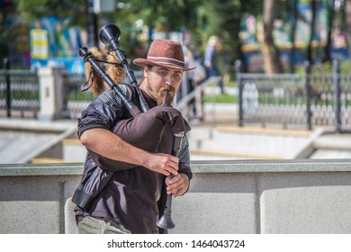 bagpipe street musician in hat, with beard and mustache