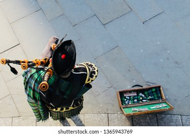 Bagpiper in Kilt and Highland Dress Playing Bagpipes Next to his Wooden Busking Case with Fridge Magnets Written and Tartan Viewed From Above on Pavement Background