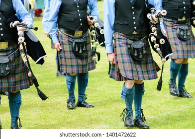 Bagpipers wearing kilts marching while carrying their bagpipes