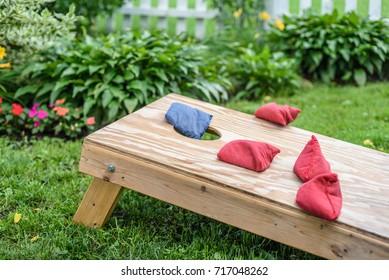 bags in air landing on cornhole board in grass in backyard