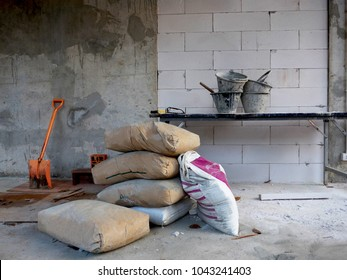 The bags of cement , shovel and cement tub on table in the construction site