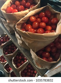 Bags of cherry tomatoes on a market shelf.