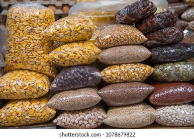 Bags of corn, quinoa, garbanzo, and other beans in Ecuadorian street market, including flax, tamarind, pumpkin, millet and other seeds.
