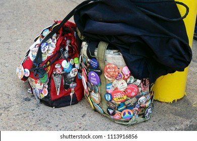 Bags covered with buttons and pins of varying liberal political slogans and social justice messages are seen at a protest.