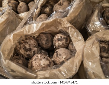 """Bags of fresh """"new potatoes"""" for sale in a shop."""