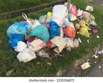 Bags of garbage on the side of a road, pollution garbage waste, lots of junk dump, plastic garbage waste is environment pollution