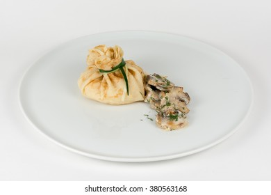 Bags of pancakes stuffed with mushrooms on white plate closeup isolated on white