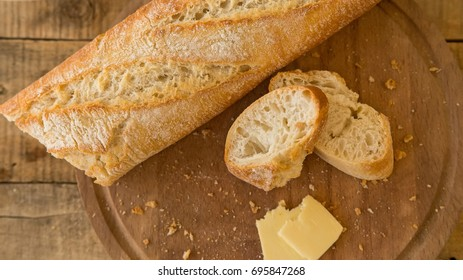 Baguete and slices of cheese on cutting board