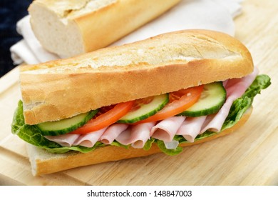 Baguette with lettuce, ham, tomato and cucumber on a wooden board