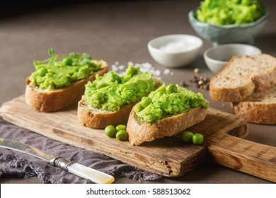 Baguette with mashed green peas and mint. Dark background. Selective focus