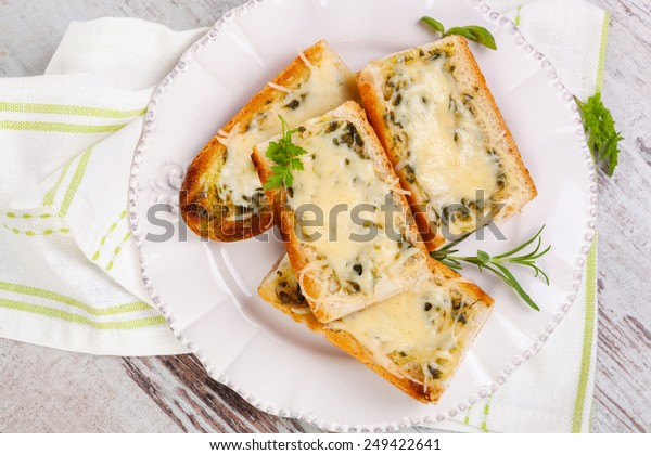 Baguette with melted cheese and fresh herbs on white wooden background, top view. Culinary eating.