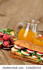Baguette sandwich with egg, arugula salad, tomatoes and radish