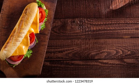 Baguette sandwich with ham, cheese, lettuce, tomatoes and onion on a cutting board. Long subway sandwich on a dark background with copy space.