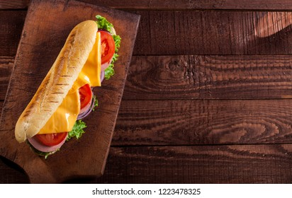 Baguette sandwich with ham, cheese, lettuce, tomatoes and onion on a cutting board. Long   sandwich on a dark background with copy space.