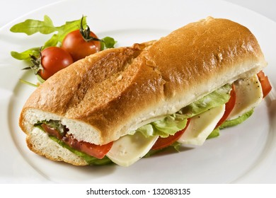 Baguette sandwich with mozzarella and tomatoes on a white plate