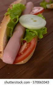 baguette with sausage and vegetables on a wooden table