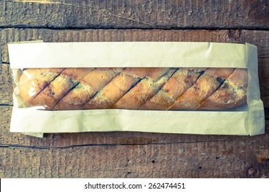 Baguette with spices in a bakery packaging. Top view