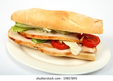 """A baguette """"submarine"""" bread roll filled with slices of turkey, lettuce and tomato on a plate."""