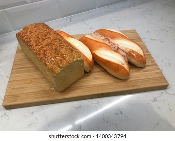 Baguette and toast on top of wooden plate.