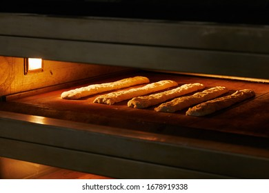 baguettes lying in a row in a large oven are baked