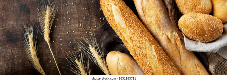 Baguettes on a brown wooden table. French bread close-up. Top view with copyspace. Banner