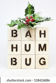 Bah Humbug spelled with toy blocks topped with holiday holly. Vertical.
