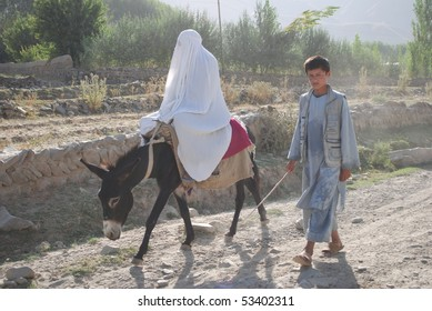 BAHARAK, AFGHANISTAN - AUGUST 12: Afghan mother from Baharak, accompanied by her teenaged son, on their way to visit family August 12, 2009 in Faizabad, Badakhshan province, northern Afghanistan.