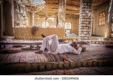 Bahariya, Egypt - April 2018: Arab man wearing white traditional clothing resting on the carpets at Bedouin house, Sahara, Egypt