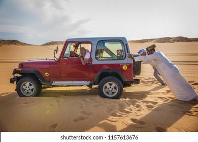 BAHARIYA, EGYPT - April 2018: Jeep car in Sahara desert, White desert of Egypt (Farafra). Arabic emn pushing the car stuck in sands, Sahara, Egypt