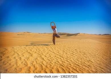 Bahariya, Egypt - April 2019: Young woman making yoga in Sahara desert, Vrikshasana ( tree pose) in Sahara, Egypt