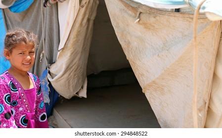 BAHARKA REFUGEE CAMP, ERBIL, KURDISTAN, IRAQ - 2015 JULY 1  - A young refugee heading into her tent in Baharka refugee camp.