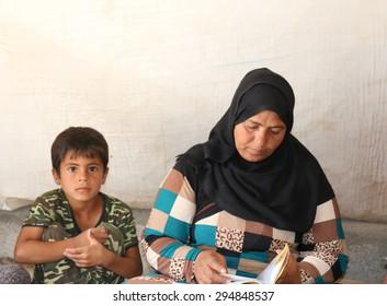 BAHARKA REFUGEE CAMP, ERBIL, KURDISTAN, IRAQ - 2015 JULY 1  - A mother with her son looking through her husband's death certificate in Baharka refugee camp.