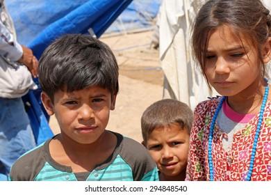 BAHARKA REFUGEE CAMP, ERBIL, KURDISTAN, IRAQ - 2015 JULY 1  - Three displaced children  in Baharka refugee camp. Baharka is home to more than 740 refugee families.