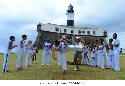 BAHIA, BRAZIL: DECEMBER 8: Bahia's traditional Capoeira group perform in front of The Farol da Barra lighthouse, on December 08, 2013 in Salvador, Brazil.