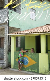 BAHIA, BRAZIL - MARCH 17, 2015: Brazilians in a small Northeastern fishing village talk over a wall decorated with a painting of the Bandeira do Brasil Brazilian flag.