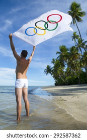 BAHIA, BRAZIL - MARCH 18, 2015: Athlete stands on rustic Brazilian beach holding Olympic flag in the wind.