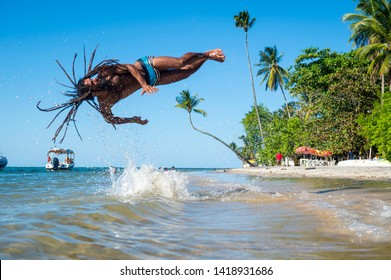 BAHIA, BRAZIL - MARCH 2018: A young athletic Brazilian man with dreadlocks does an acrobatic flip into the sea on the shore of a remote village beach.
