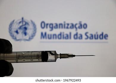 Bahia, Brazil - May 3, 2021: World Health Organization (Organização Mundial da Saúde, in portuguese) logo displayed on a screen and hand holding a syringe. Covid-19 vaccine concept.