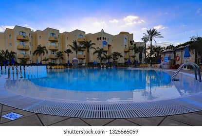 Bahia Feliz,Gran Canaria,02.03.2019. Early dawn view of the building of Monte Feliz hotel with pool in the foreground.This popular apartment complex situated amongst green gardens,close to the beach.