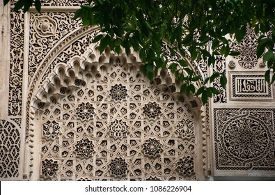 Bahia palace marrakech morocco. Detail wall with branch in front. Old architecture. Ornament wall with cultural islamic detailed ornaments.